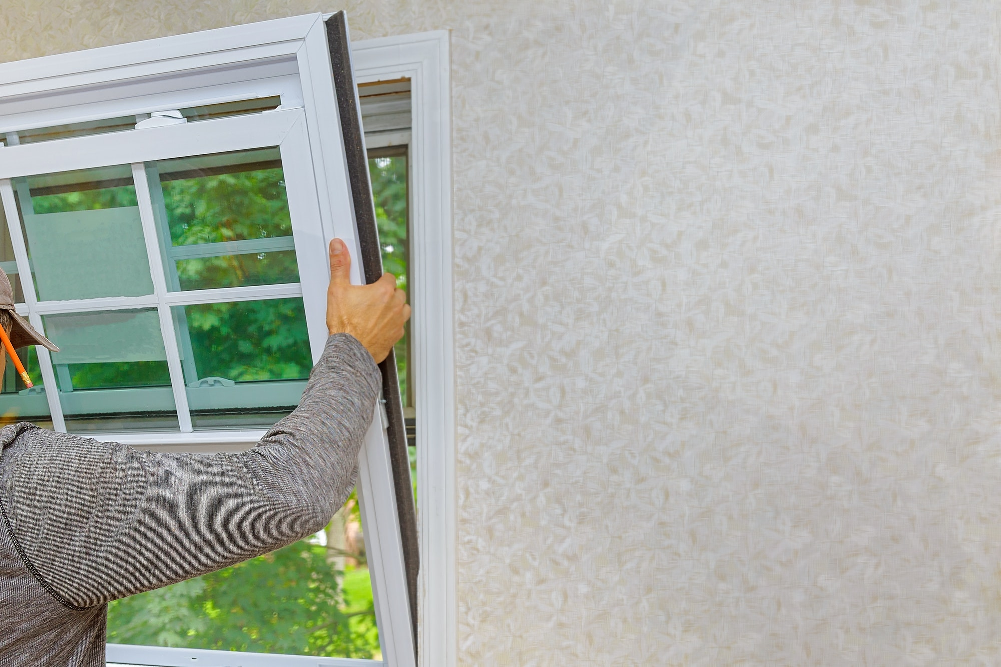 Window installer installing replacement windows in Akron, Ohio house
